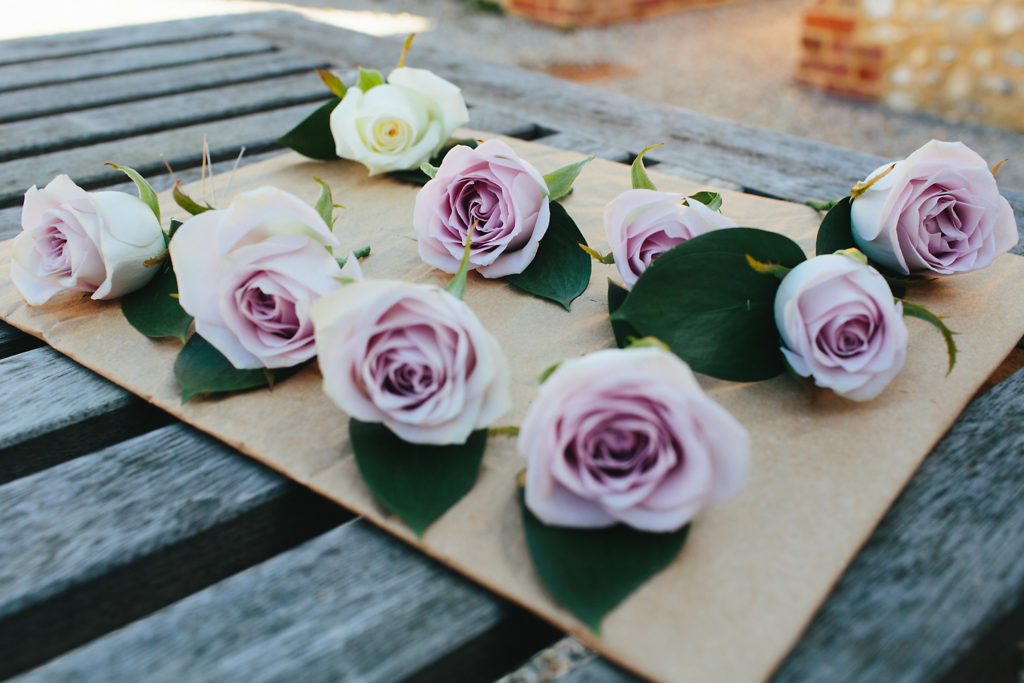 Lilac buttonholes on a wooden table