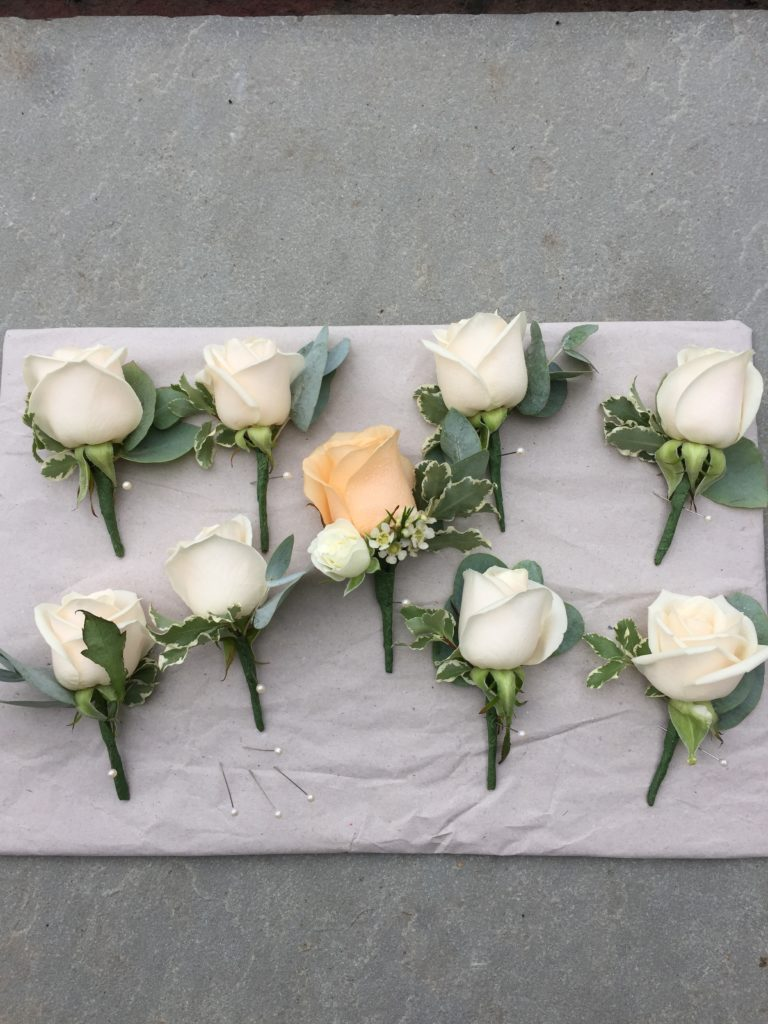Ivory and peach rose buttonholes with leaves