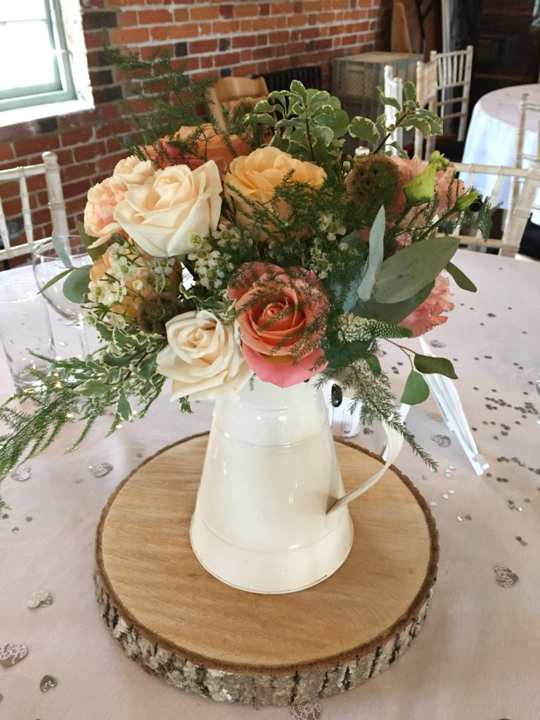 Cream jug with flowers on a log slice