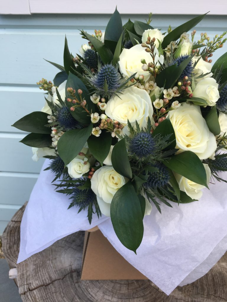 White rose bouquet with blue thistles