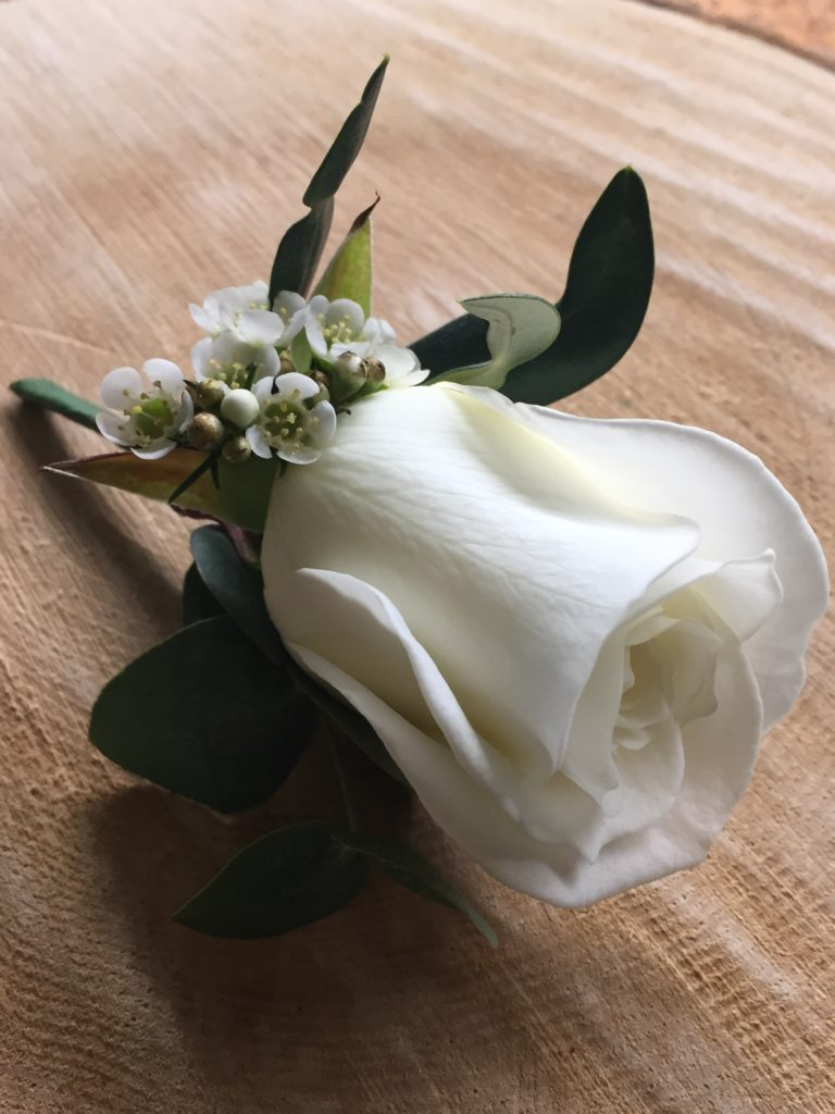 White rose buttonhole on a log slice