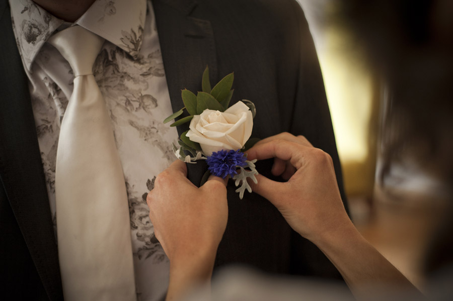 White rose buttonhole being pinned on to black suit