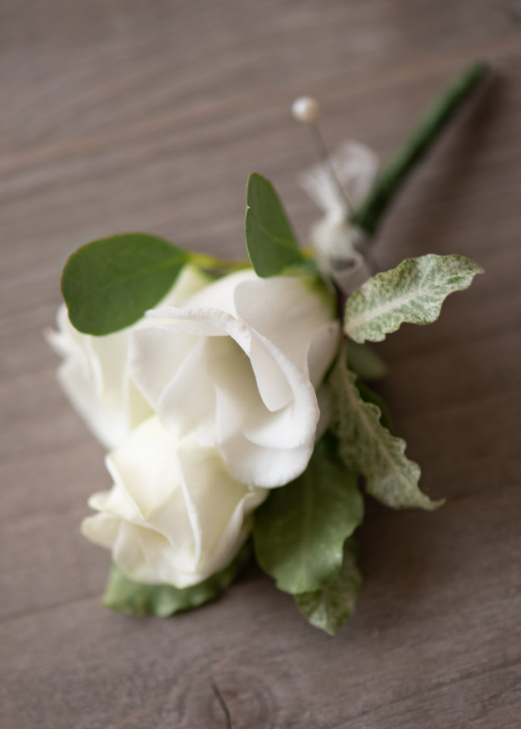White flower buttonhole with pin