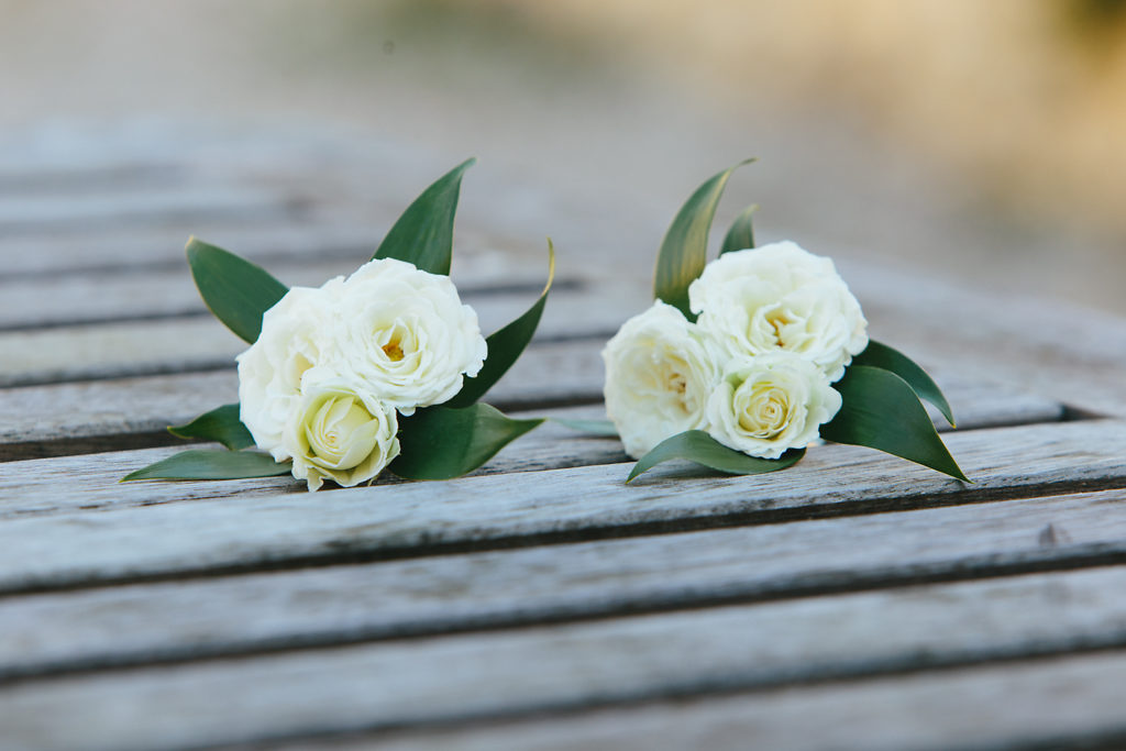 White corsages with leaves on a wooden table