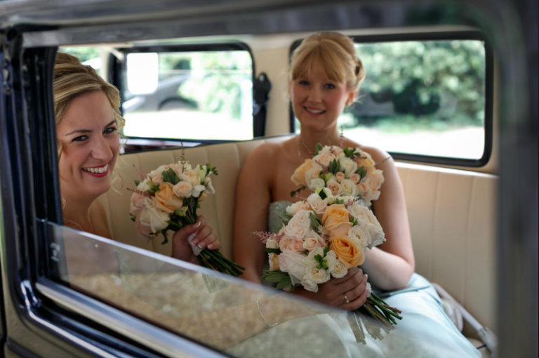 Bridesmaids sitting in vintage car holding bouquets
