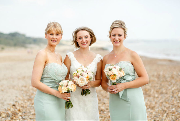Bride and bridesmaids standing on the beach with bouquets