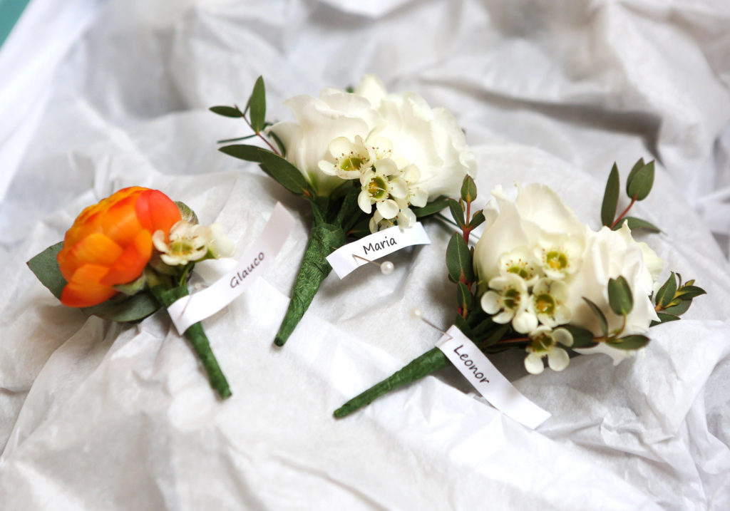 white and orange wedding buttonholes